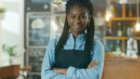 Beautiful African-American Cafe Owner Standing with Crossed Arms and a Smile in Her Stylish Coffee House. Shot on RED EPIC-W 8K Helium Cinema Camera.