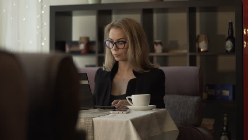 Young businesswoman in glasses typing on keyboard notebook sitting at couch in cafe with coffee cup. Beautiful woman using laptop for work during business lunch in modern cafe | Shutterstock HD Video #33995971