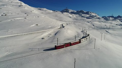 Bernina express on Bernina Pass. Winter season, red train and snow