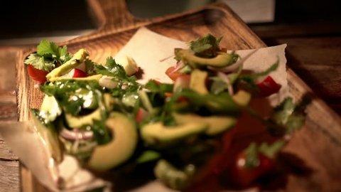 A fresh avocado salad with chopped tomatoes, onions, radish, cucumber, fresh coriander and arugula on a wooden cutting board under warm muffled light, close-up.