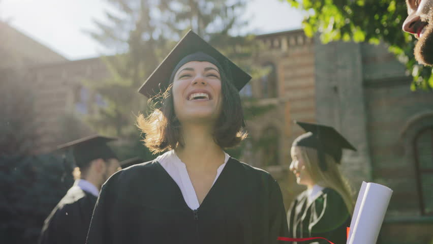 Young multi ethnical graduates in caps laughing out loud and having fun on their graduation day. Outdoors. Close up | Shutterstock HD Video #34025368