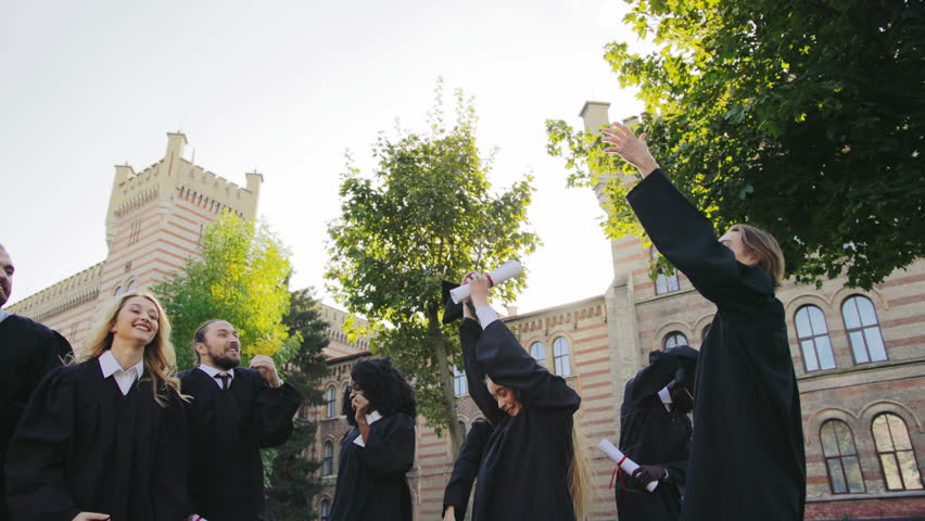 Group of mixed races female and male graduates tossing their black caps up in the air cheerfully on the graduation day. Outdoors