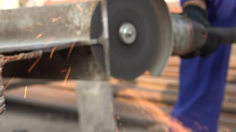 A kind of worker with an old electric tool that creates metal beam in factory among the iron beams