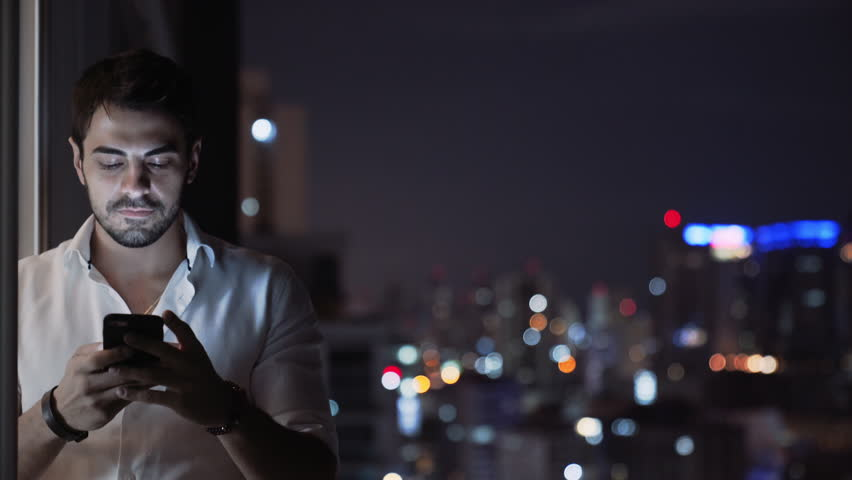 A Young Handsome Man Smiles While he Sends a Voice Message Using His Mobile Phone App, Standing at Night in  Balcony with Tall Building Skyline Lights. Technology apps ios android Communication 4k UHD