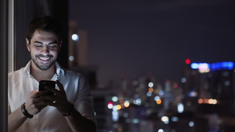 A Young Handsome Man Smiles While he Sends a Voice Message Using His Smartphone, Balcony at Night with Tall Building Skyline Lights. Man With Phone Texting and Chatting with App. Technology. Copyspace