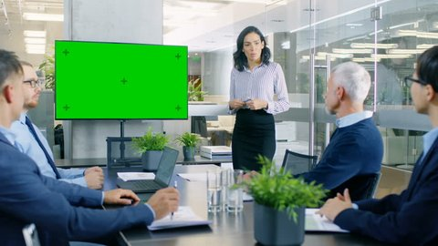 Beautiful Businesswoman Gives Report/ Presentation to Her Business Colleagues in the Conference Room, She Interacts with Wall TV with Green Chroma Key Screen.