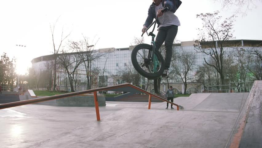 BMX rider doing tricks in street plaza, bicycle stunt rider in cocncrete skatepark, super slow motion #34094188