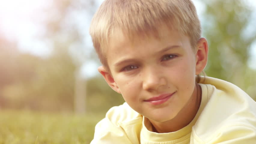 Closeup portrait of a boy looking through binoculars in sunny lights