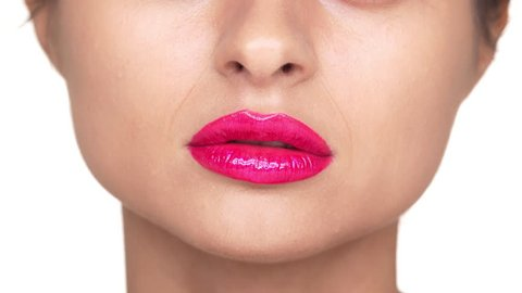 Extreme closeup portrait of serious woman wearing dazzling pink lipstick expressing shock with opening her mouth over white background. Concept of emotions