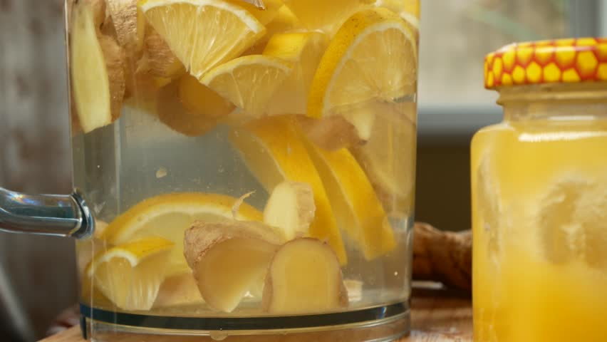 someone makes a handmade drink from lemons, ginger root and pineapple. 4k