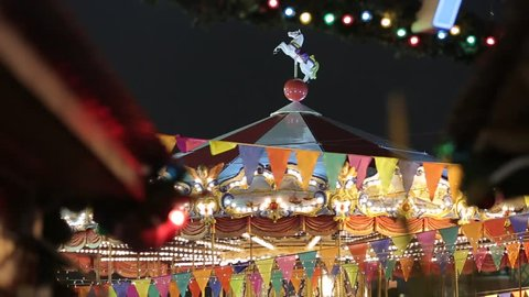Christmas Fair. Multicolored carousel is spinning in amusement park, colorful illuminated carousel with colorful lights, Holiday. Night time