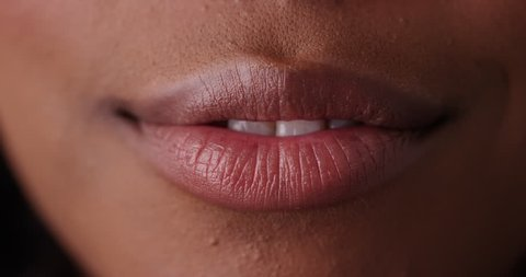 Extreme close up of black woman's lips blowing kiss on green screen. Close up of pretty mouth smiling on greenscreen to be keyed or composited.