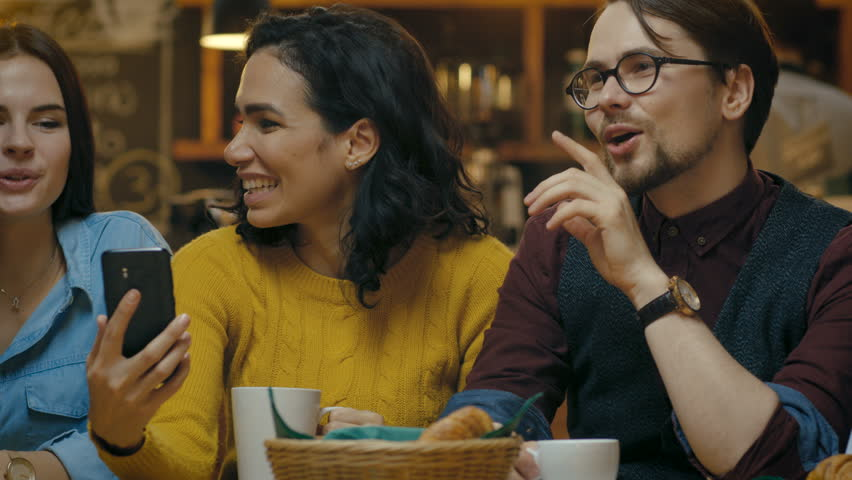 Beautiful Hispanic Woman Shows Interesting Stuff on Her Smartphone to Her Friends while They Have Good Time in Bar. They Laugh, Joke, Drink in Stylish Hipster Bar Establishment. | Shutterstock HD Video #34161088