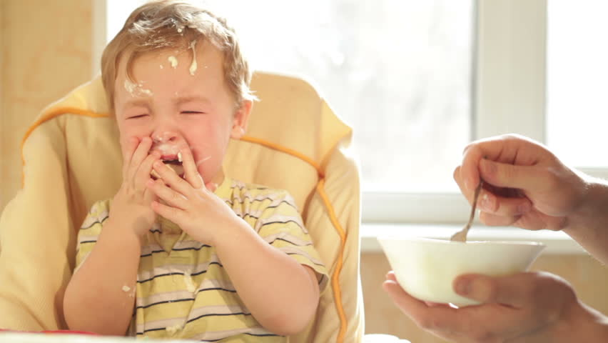 Little boy is crying because he doesn't want to eat more cereal. | Shutterstock HD Video #3417038