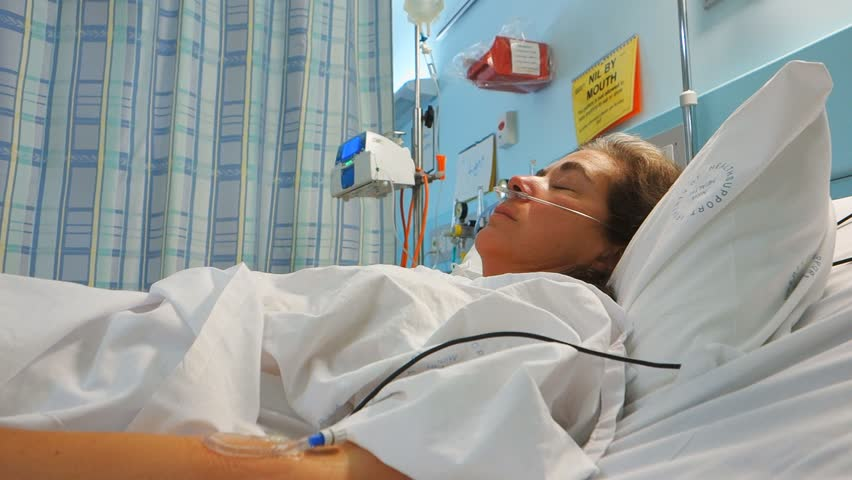 a female patient rests in a hospital bed