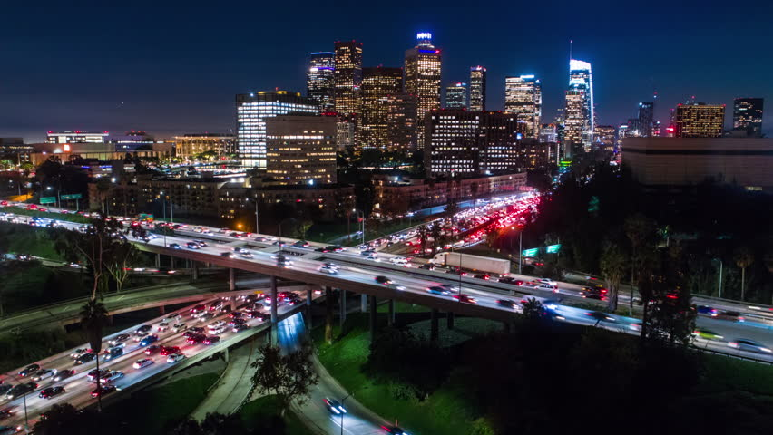 Cinematic urban aerial time lapse in motion of downtown Los Angeles freeways with heavy traffic, city skyline and sky scrapers at night with deep blue sky