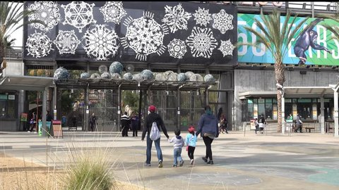 LOS ANGELES, CA / USA - December 22, 2017: Visitors are shown approaching the L.A. Zoo entrance, then the view tilts up to show the zoo's sign. For editorial uses only.