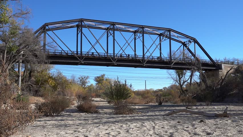 Pedestrians on a park trail walk across a former train bridge that spans a dry creek bed.