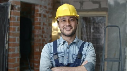 PAN of cheerful young Asian builder in hard hat standing with crossed arms in unfinished building and smiling for camera