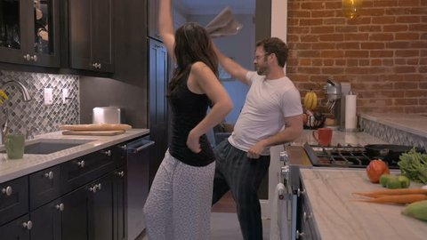 Successful happy handsome man and gorgeous woman in early 30s dancing together in their modern kitchen in slow motion