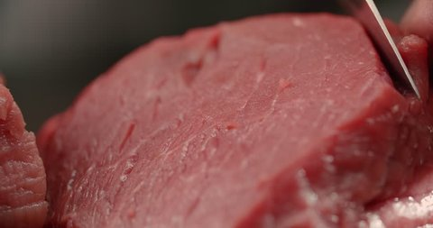 the chef cut raw meat beef fillet, makes the preparation for cooking, Dolly shot, close-up