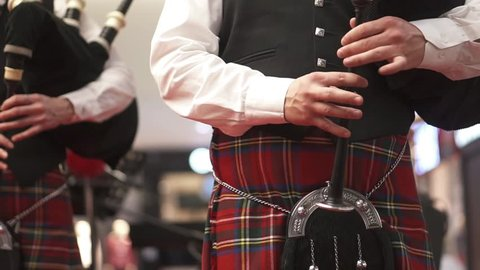 A man in a Scottish kilt is playing on a bagpipe. Concert. Bagpipes. A man in checkered clothes. Musician at the concert.