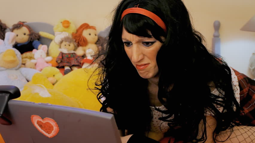A girl on a bed, chatting on her laptop, showing a disgusted face.