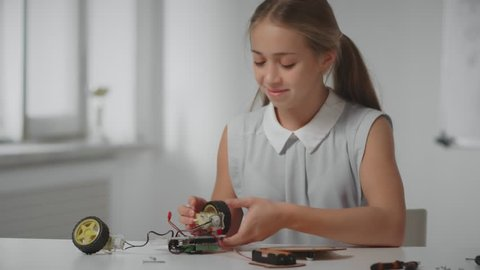 School girl constructing model bot car at table in modern laboratory at class