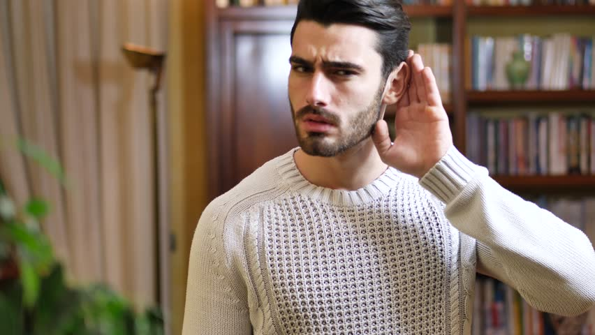 Handsome young man can't hear, putting hand around his ear. Indoors shot inside a house