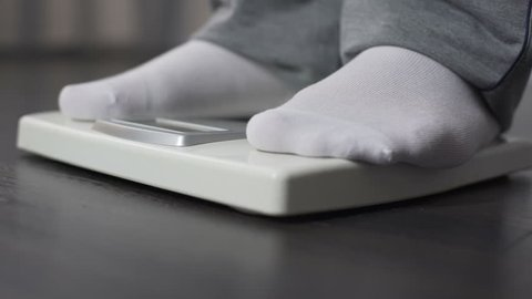 Obese man measuring his weight on health scale, dieting and weightloss, close-up