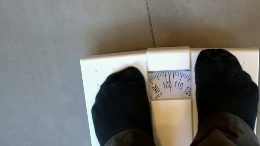 A fat man in black socks is weighed on a household scale. The monitor weighs 102 kg   Shutterstock HD Video #34371058