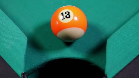 Macro shot of an orange snooker ball with number thirteen get into the billiard pocket