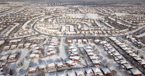 Low altitude drone flight over suburban neighborhood (Oakville, Ontario, Canada) after a snow storm. Houses and roofs are all white with snow.