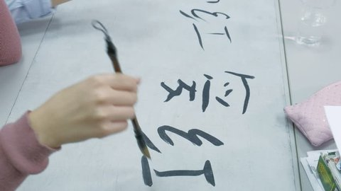 Woman teaching teen how to write Chinese characters at calligraphy class. Student learning writing with brush, ink, and paper and teacher helping her. School, education 4k