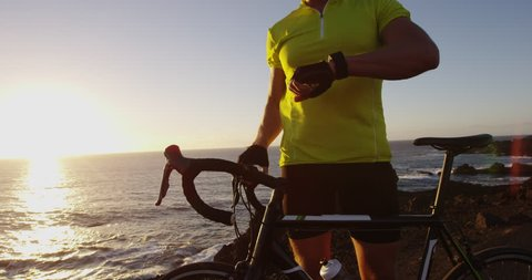 Cyclist biking looking at smartwatch while cycling riding road bike. Athlete biker using activity tracker gps fitness watch on workout at sunset. Sports man using his watch app for fitness tracking.
