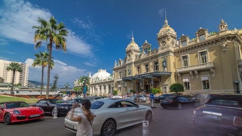 Grand Casino in Monte Carlo timelapse hyperlapse, Monaco. historical building. Parking in front of entrance. Palms on the side. Blue cloudy sky at summer day