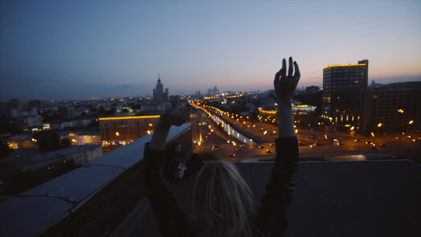 couple in rock n roll style on the rooftop enjoing night city light, young with raised and waving hands walking at city light background, concept of happy young people slowmotion shot