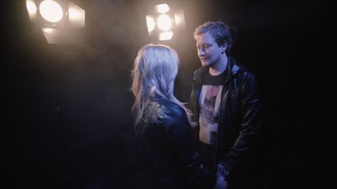 couple in rock-n-roll style, young couple on scene in spotlight kissing at dark background and backlight