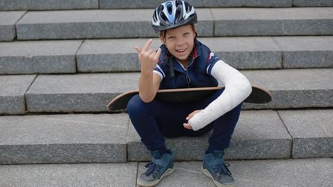 White boy with broken arm makng the rock sign sitting on the granite stairs with his skateboard.