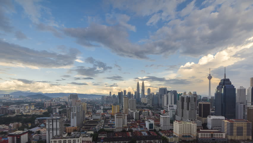 4K Time lapse: Dramatic Kuala Lumpur city view during monsoon tropical season with rainbow and rain clouds overlooking the city skyline. Camera Move to Right, Timelapse.