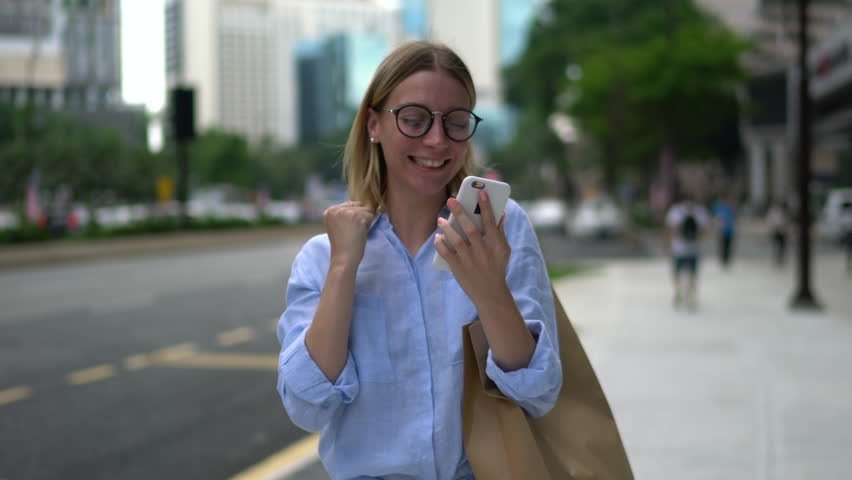 Happy excited young woman receiving discount for shopping while checking email box on mobile calling for sharing success with friend while walking in urban setting down street