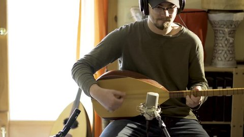 Camera slides to right as young man wearing headphones playing baglama saz with microphones in front of instrument and oud and darbuka drums in background in a room with a lot of light.