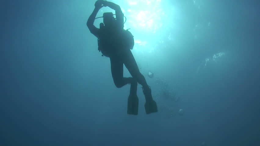 A scuba diver moves with slowly kicking fins through the blue water