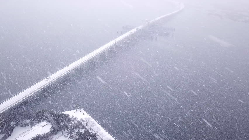 Aerial view of icy bridge over water during blizzard.