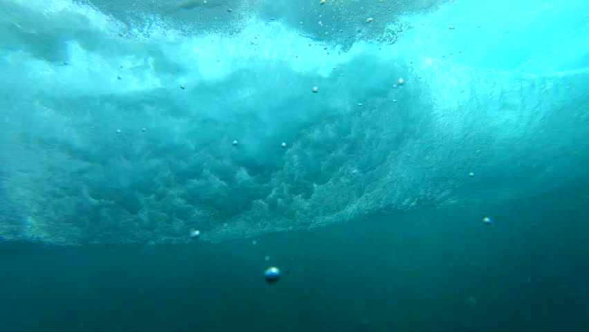 SLOW MOTION, LENS FLARE, UNDERWATER: Big barrel wave rushing towards peaceful rocky tropical island. Camera descends from sunny beaches to deep crystal clear water below a large bubbling ocean wave.