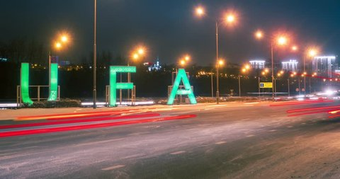 Timelapse of sign Ufa and transport traffic on main road into city in the winter night. Bashkortostan, Russia.