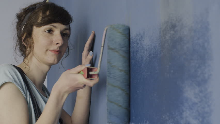 Painting walls with roller.  A young woman painting walls in a blue bedroom in her home with a roller. Close up.