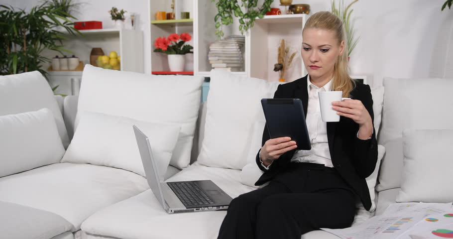 Business Woman Reading Daily News from Digital Tablet Drinking Coffee Home Sofa - 4K stock video