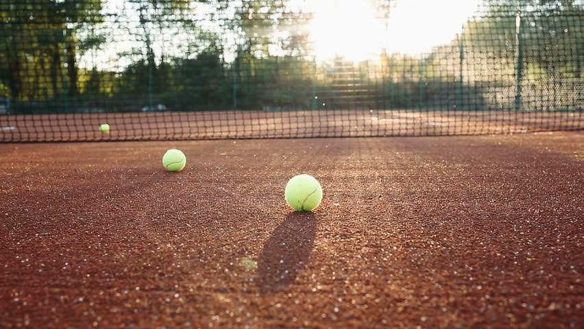 Tennis balls along tennis clay court