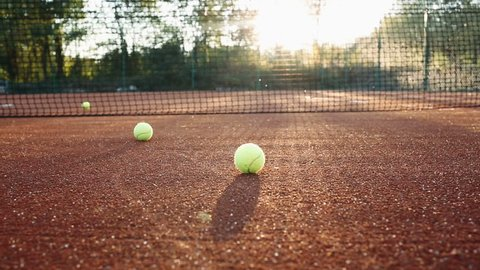 Tennis balls along tennis clay court